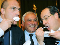 Italian ministers eat the cheese during a press conference