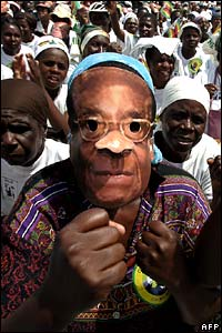 Man wears a Mugabe face mask at a rally for President Mugabe's Zanu-PF party.