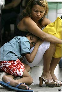 A mother with her son, who is suffering from dengue-like symptoms, waits for treatment in Jacarepagua, in Rio de Janeiro, on 27 March
