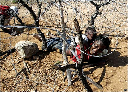 A woman and baby crawl under barbed wire from Zimbabwe to reach South Africa on 28 March
