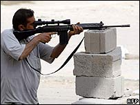 A Mehdi Army militiaman aims his rifle in Basra on 29 March