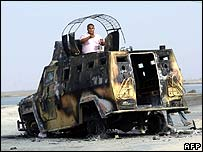 A man inspects a charred Iraqi army vehicle in Basra on 29 March
