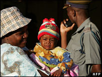 A policeman and voter and her baby at a polling station in Zimbabwe