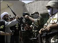 What appear to be Iraqi soldiers hand weapons to a Shia cleric in Sadr City, Baghdad, on 29 March