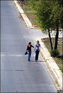 Two young women walk down an empty Baghdad street on 30 March