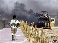 A gunman approaches a burning Iraqi army vehicle in Basra on 30 January