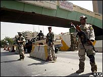 Iraqi soldiers man a checkpoint in Baghdad on 30 March