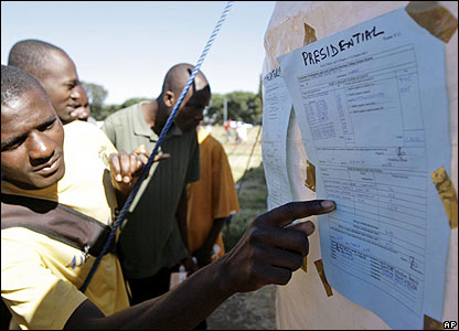 Zimbabweans look at election results taped to a tent in the Harare suburb of Mbare on 30 March