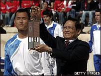 El presidente del Comité Olímpico de China, Liu Qi, muestra la lámpara que contiene la llama olímpica.
