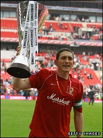Milton Keynes Dons captain Keith Andrews lifts the Trophy