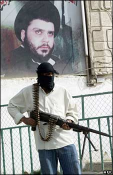 An armed Mehdi Army fighter stands under a portrait of Moqtada Sadr in Baghdad. File photo