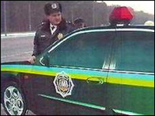 A police officer in the Ukraine with the metal car replica