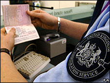 An immigration officer checking a passport at a British airport