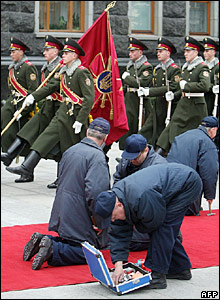 Men laying red carpet for George Bush in Ukraine