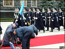 Ukrainian workers prepare the red carpet ahead of President Bush's visit
