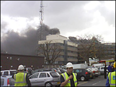 Workmen outside the burning building (Pic Dave Evans)