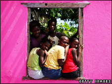 Children peer out of a window in Kingston, Jamaica