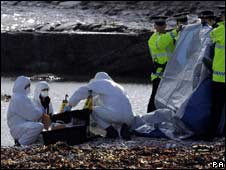 Police officers shield forensic officers on Arbroath beach in Angus, where the severed head of a woman has been found
