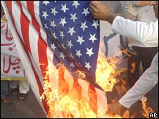 Pakistani protesters burn a US flag to protest against a visit by US officials, March 2008