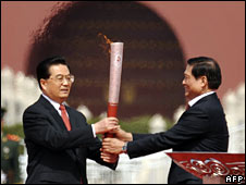 Beijing Olympics committee head Liu Qi (R) hands the torch to Chinese President Hu Jintao (L) on 31 March 2008