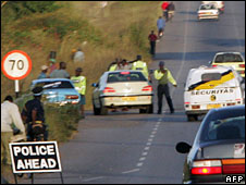 Police inspect a car at one of several road blocks set up around Harare on 1 April, 2008