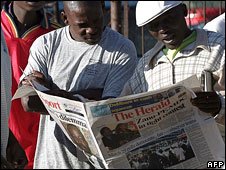 Zimbabweans reading a newspaper
