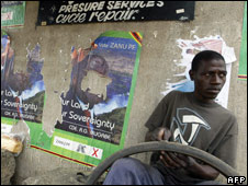 Tyre fixer next to Mugabe posters in Harare, 2 April 2008