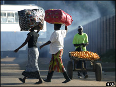 Women and man pushing cart in Harare, 1 April 2008