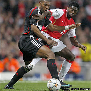 Ryan Babel shields the ball from Arsenal's Kolo Toure d