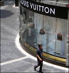 A man walks past a Louis Vuitton shop in central Bangkok