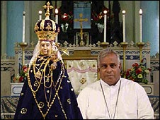 Priest beside the statue of the virgin Mary at Madhu shrine