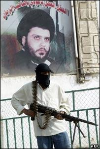 Mehdi army militiaman in front of picture of Moqtada Sadr, Sadr City, Baghdad