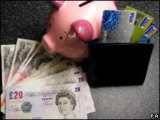 A piggy bank, cash and bank cards