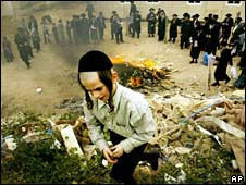 Ultra-Orthodox Jews gather around a fire as they burn leavened items in Jerusalem.