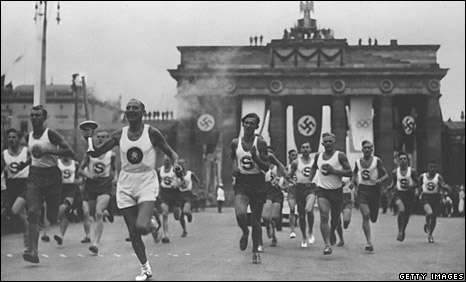 A torch bearer passes the Brandenburg Gate, Berlin, 1 August 1936