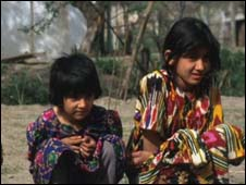 Tajik children sitting on a pavement