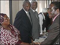 Robert Mugabe (der.), reunido con jefes de su partido