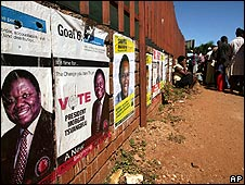 Zimbabweans wait in line for food in Harare on 4 April by a wall with election posters