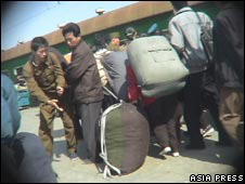 North Koreans carrying luggage (image: Asia Press)