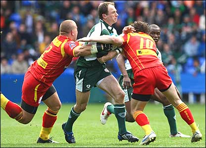 London Irish captain Mike Catt is tackled by Perpignan's Marius Tinou and Nicolas Laharrague