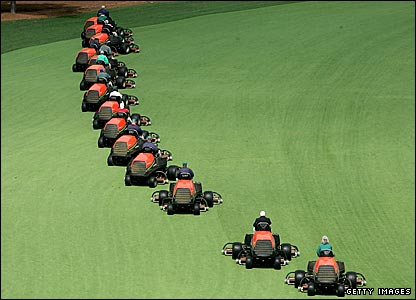 Greenkeepers manicure the Augusta fairways