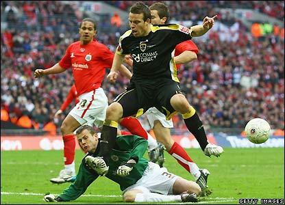 Rae hurdles Barnsley goalkeeper Luke Steele