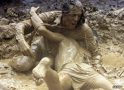 Men wrestling in the mud