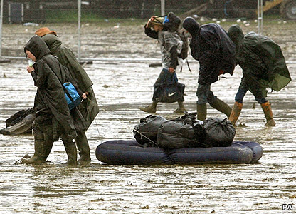 Festival goers dragging belongings through mud