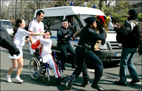 A protester is prevented from reaching a wheelchair athlete carrying the flame 7/4/08