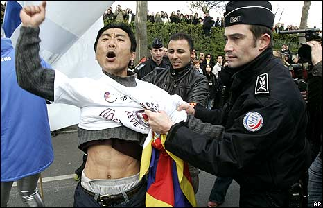 Protester is detained by police in Paris 7/4/08