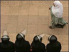 An Egyptian woman walks past riot police in Cairo on Sunday