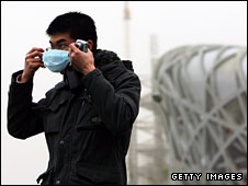 A tourist puts on a pollution mask in Beijing