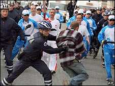 A protester gets close to an Olympic torch relay runner in Paris - 7/4/2008