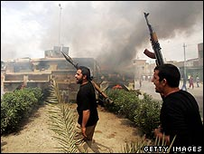 Militiamen loyal to Moqtadr Sadr celebrate after destroying an Iraqi army vehicle in Baghdad on 6 April